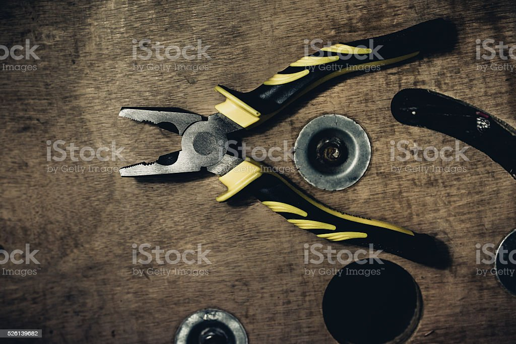 Pliers on the old wooden background stock photo