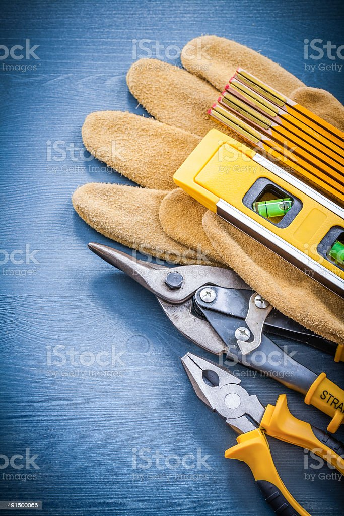 Pliers tin snips wooden meter construction level protective glov stock photo