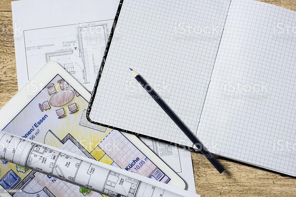 Pläne auf Architektenschreibtisch, Vergösserung auf Tablet stock photo