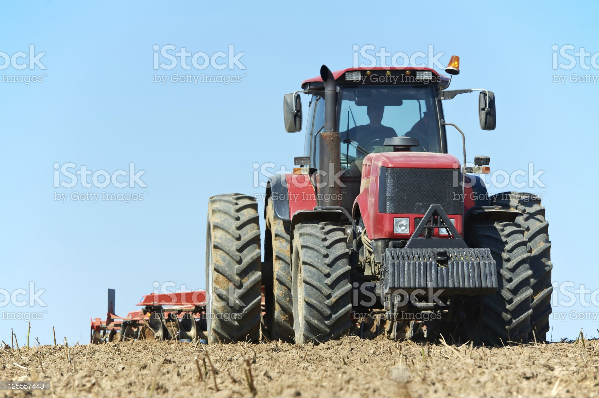A ploughing tractor with farmer at field cultivation to work royalty-free stock photo