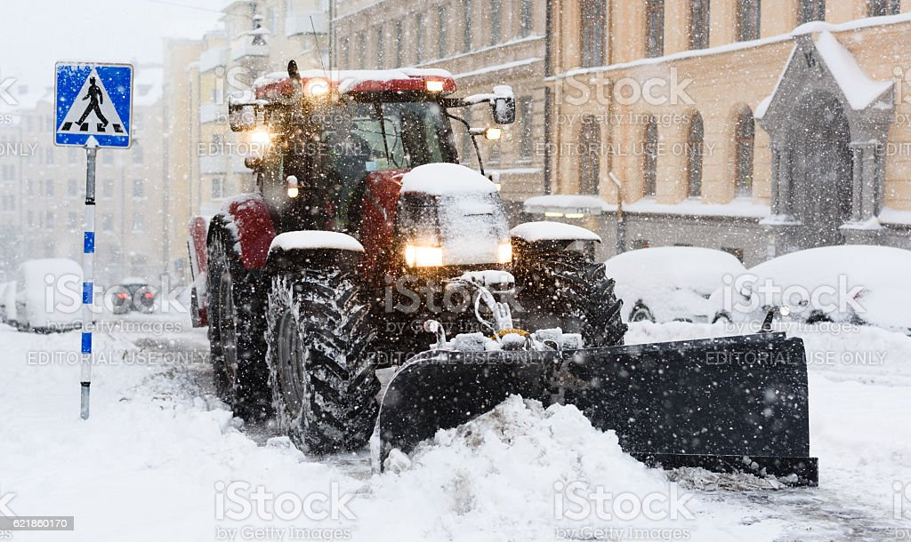 Plow removing snow from city street in Stockholm stock photo