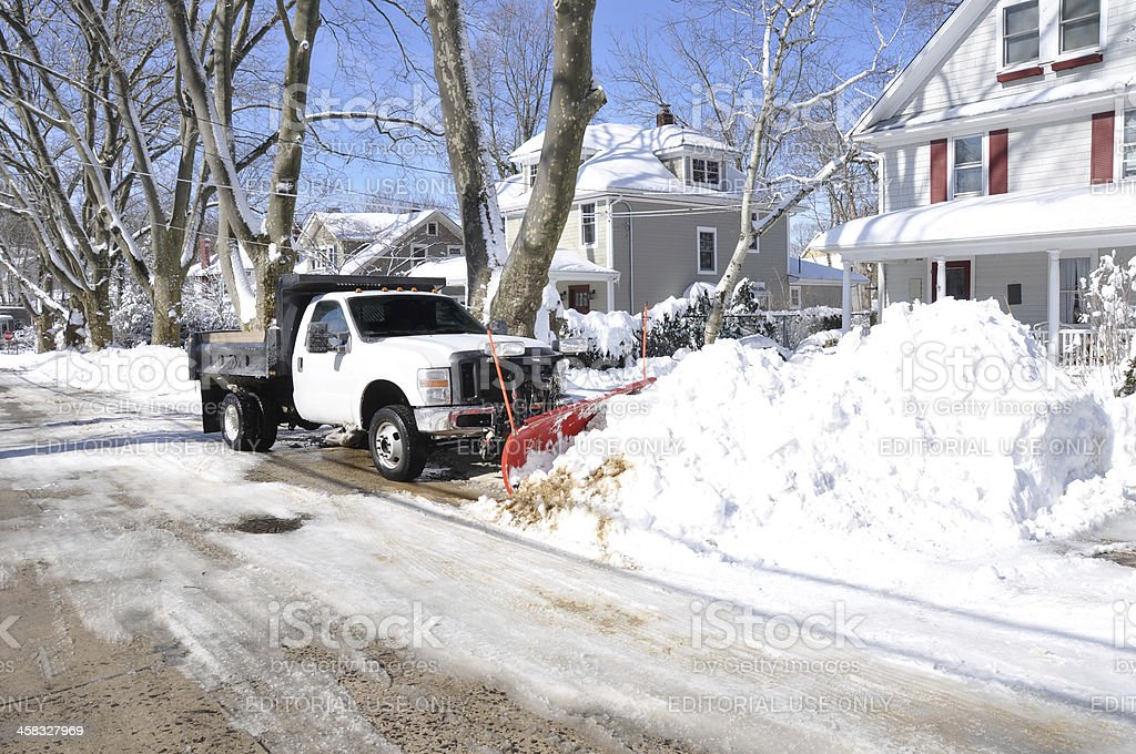 Plow Truck Cleaning Snow Filled Suburban NeighborhoodStreet stock photo