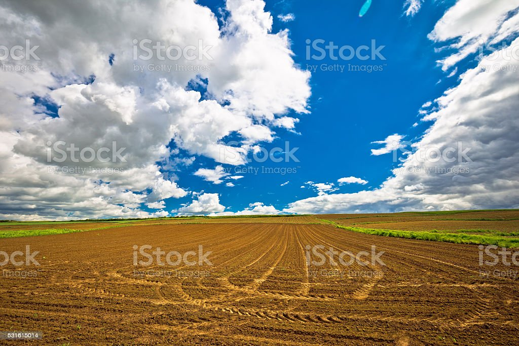Plowed field under dramatic sky view stock photo