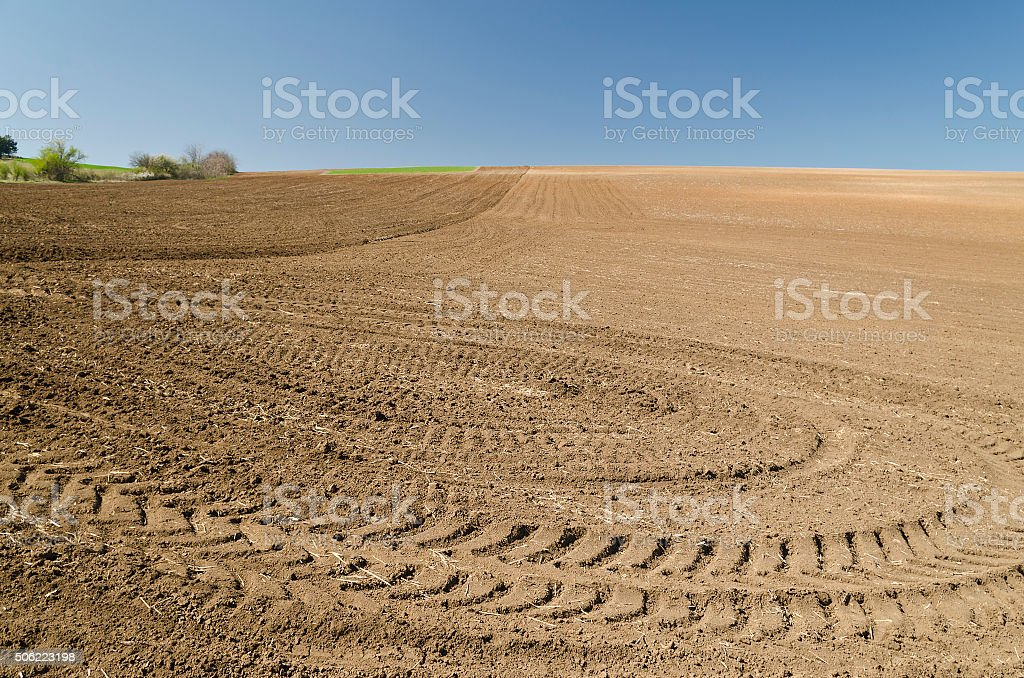 Plowed field with tractor traces in spring time stock photo
