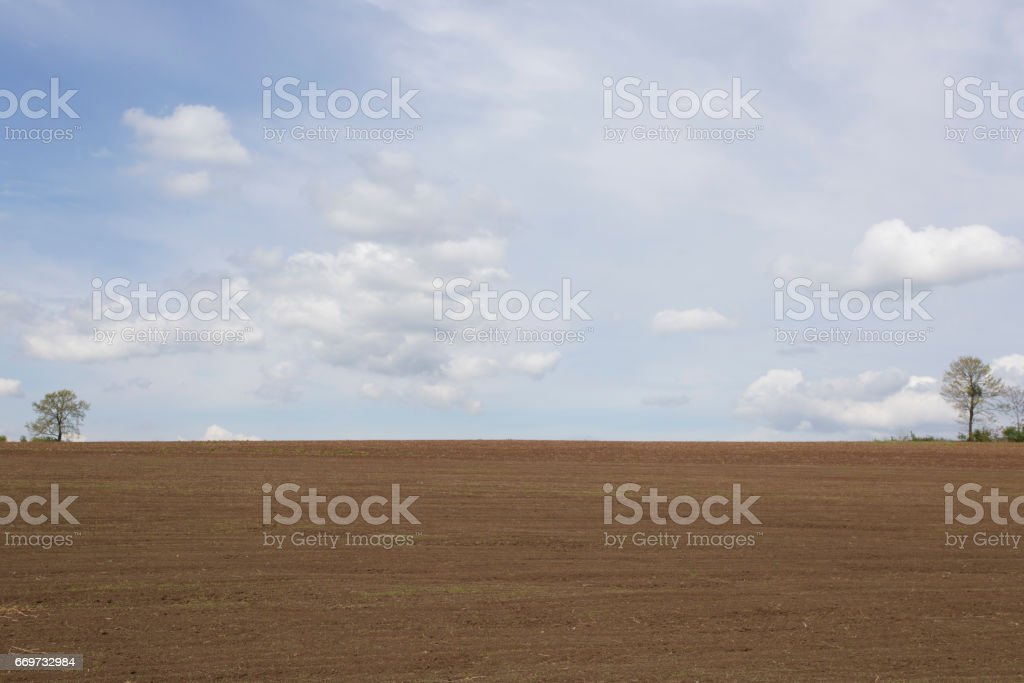 Plowed flat agriculture field prepared for sowing on sunny day springtime stock photo