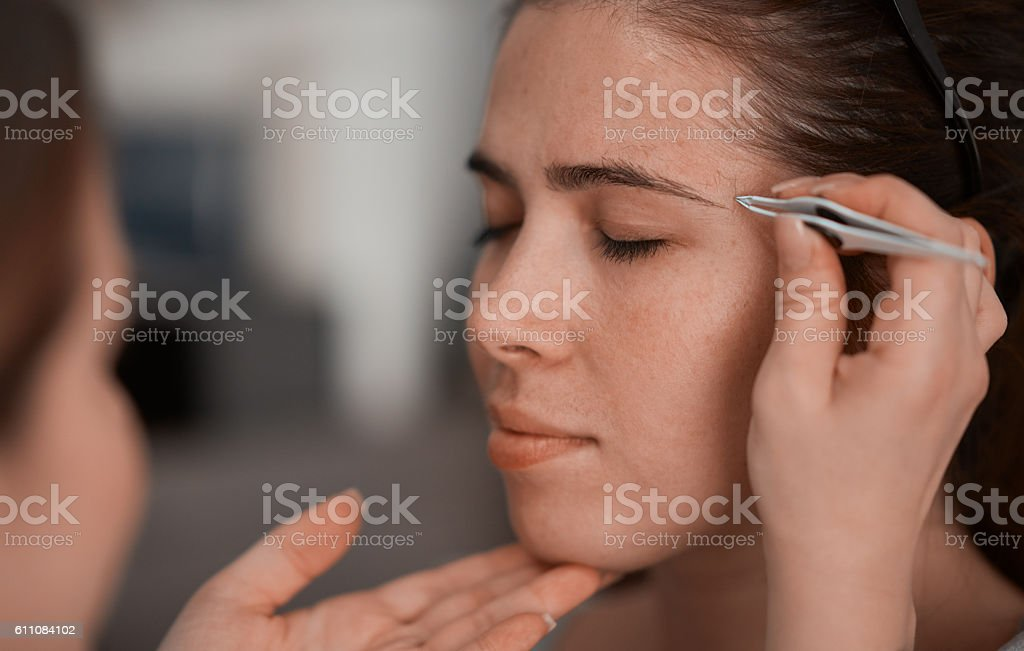 plucking eyebrow stock photo