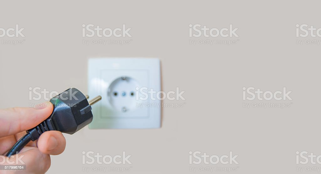 Plugging in an electric plug into a socket stock photo