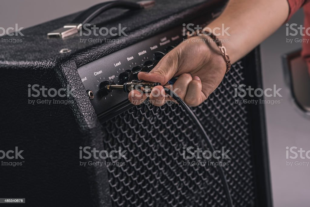 Plugging in guitar amplifier stock photo