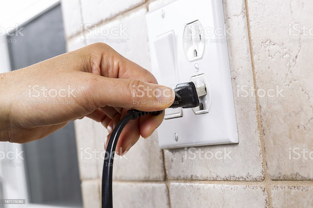 Plugging into Electrical Outlet stock photo