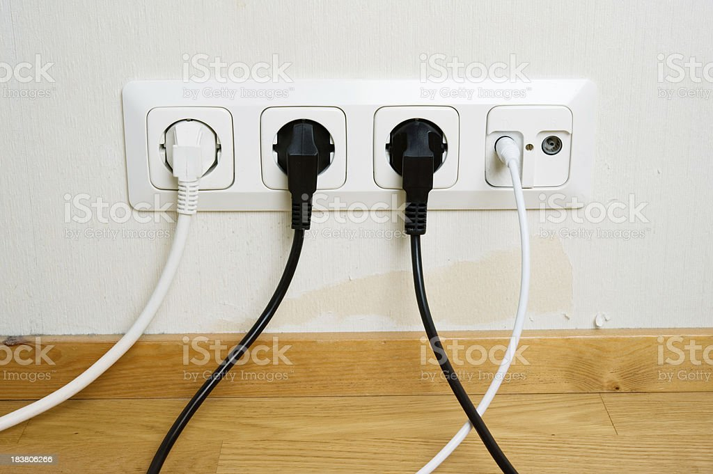 Plugs connected to the outlet in a wall royalty-free stock photo