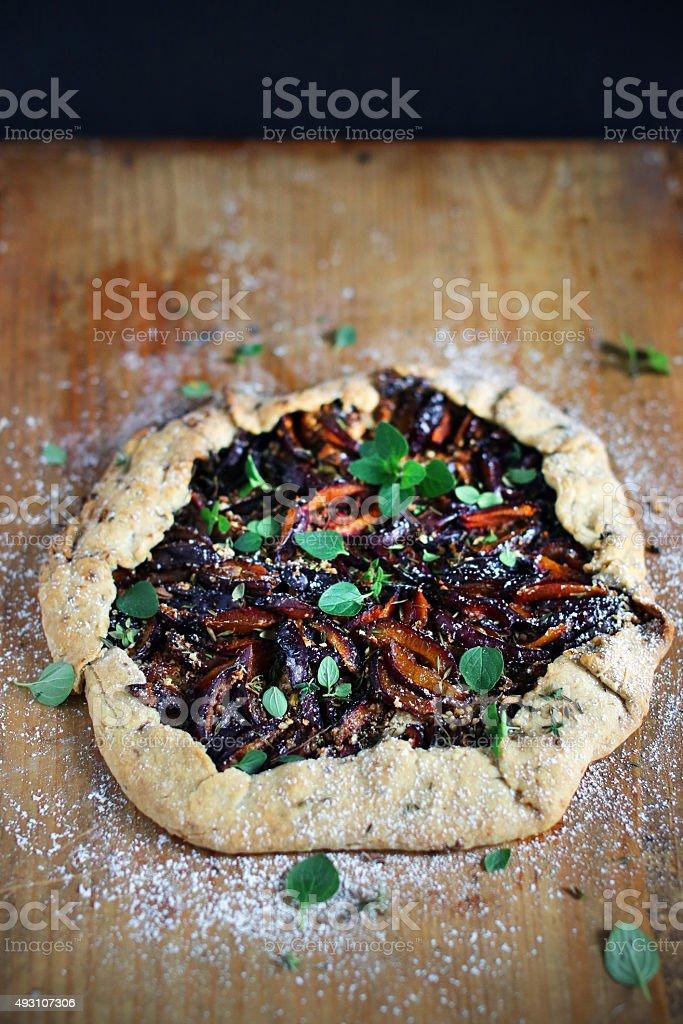Plum and marjoram tart or galette, fresh baked pie dessert stock photo