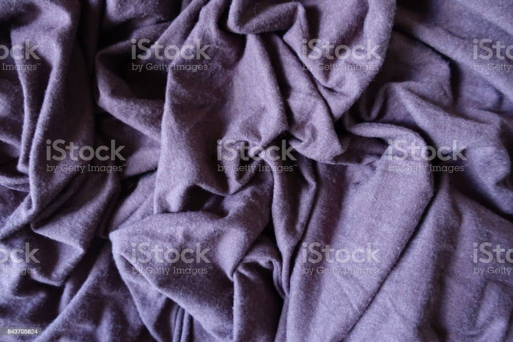 Plum colored simple stockinette fabric in folds stock photo