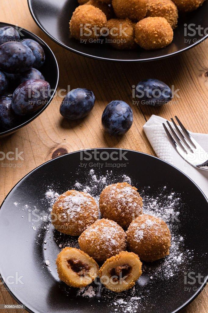 plum dumplings on black plate stock photo