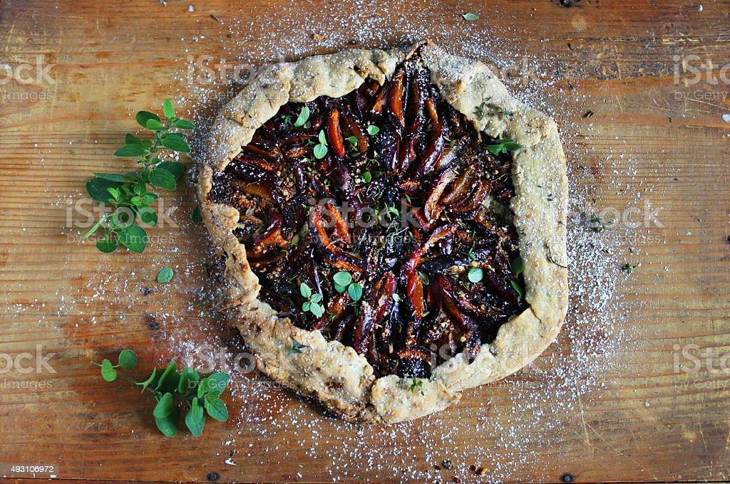Plum galette pie with wine, almonds and marjoram stock photo
