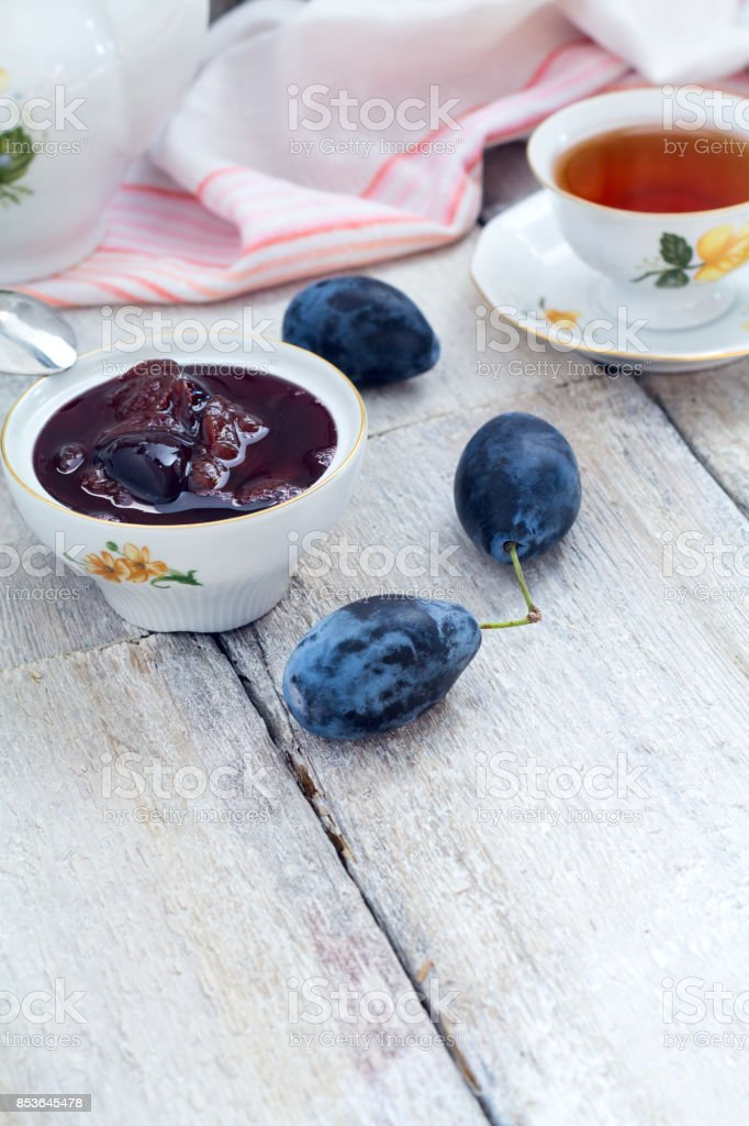 Plum jam in a bowl on a wooden table stock photo