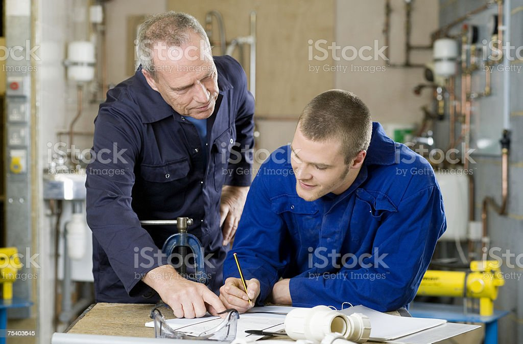 Plumber and apprentice stock photo
