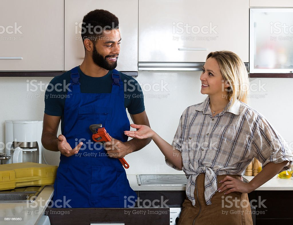 plumber and housewife in kitchen stock photo