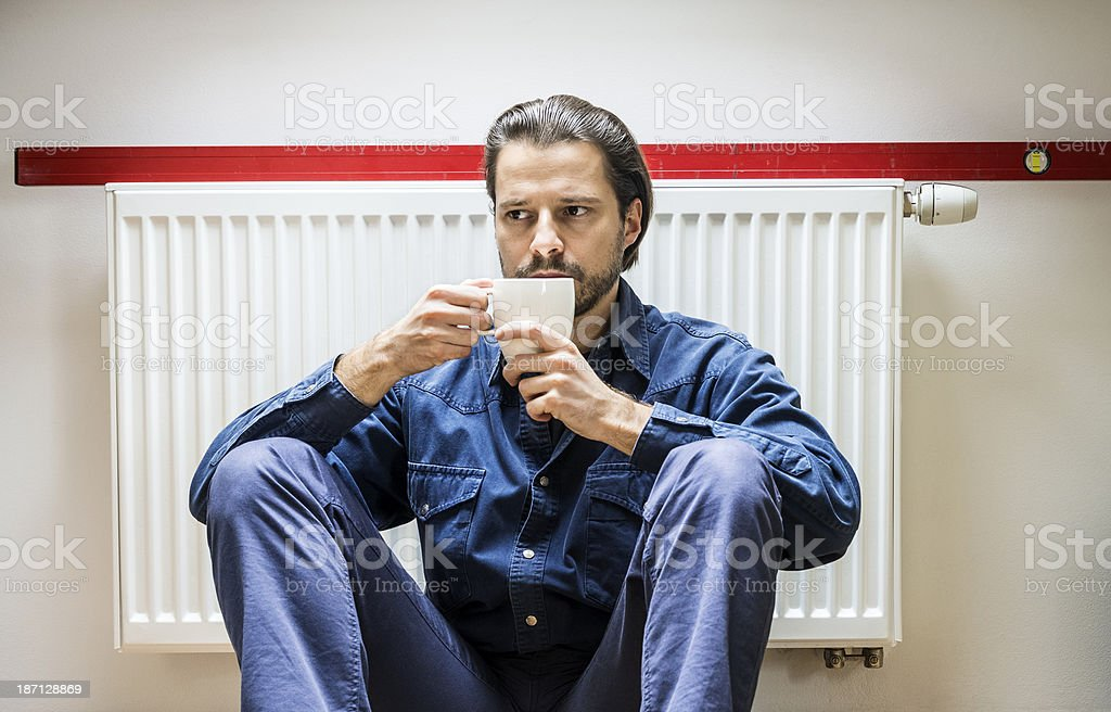 Plumber at work, drinking coffee, sitting under the heater royalty-free stock photo