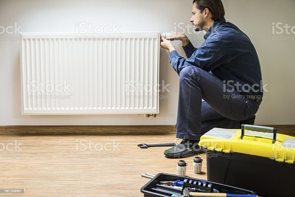 Plumber at work, fixing radiator and thermostat royalty-free stock photo