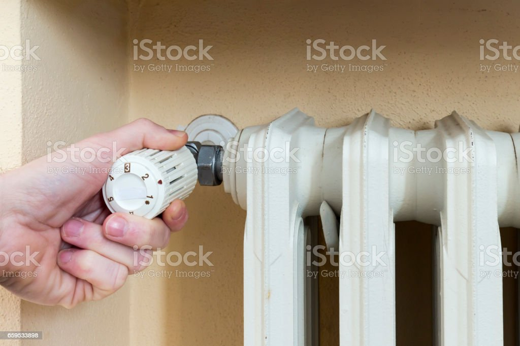Plumber at work installing a thermostatic valve on a radiator stock photo