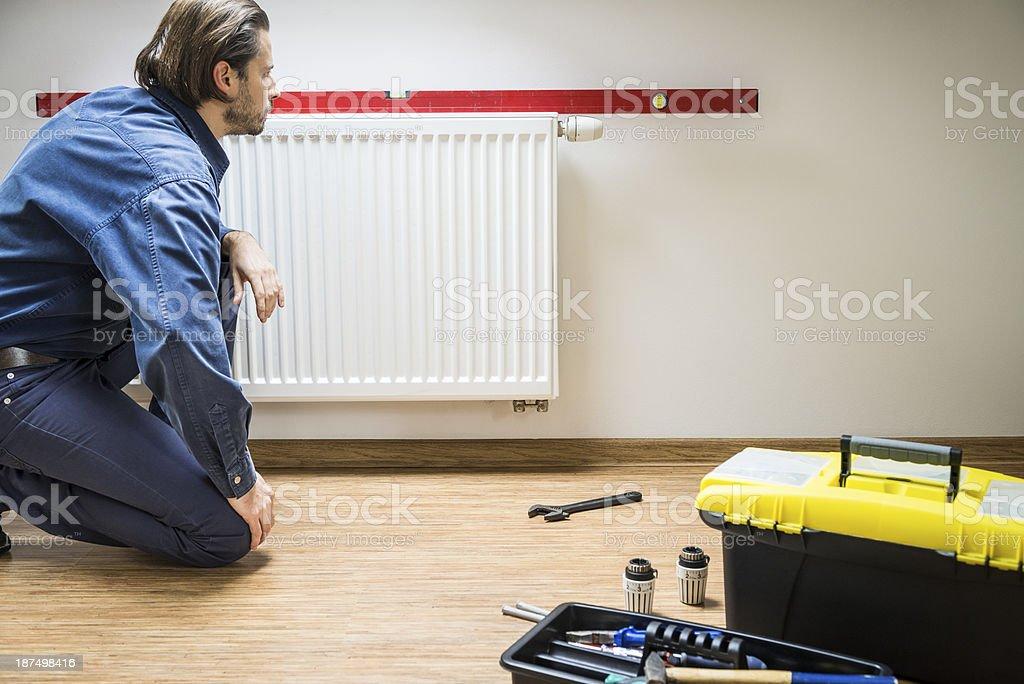 Plumber at work, installing new radiator, measuring level royalty-free stock photo