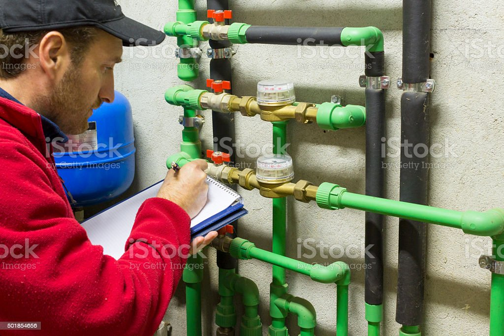 plumber at work making the consumption metering stock photo
