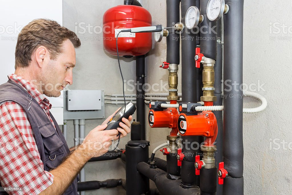 Plumber at  work measures the temperature in a boiler room stock photo