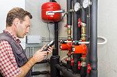 Plumber at  work measures the temperature in a boiler room