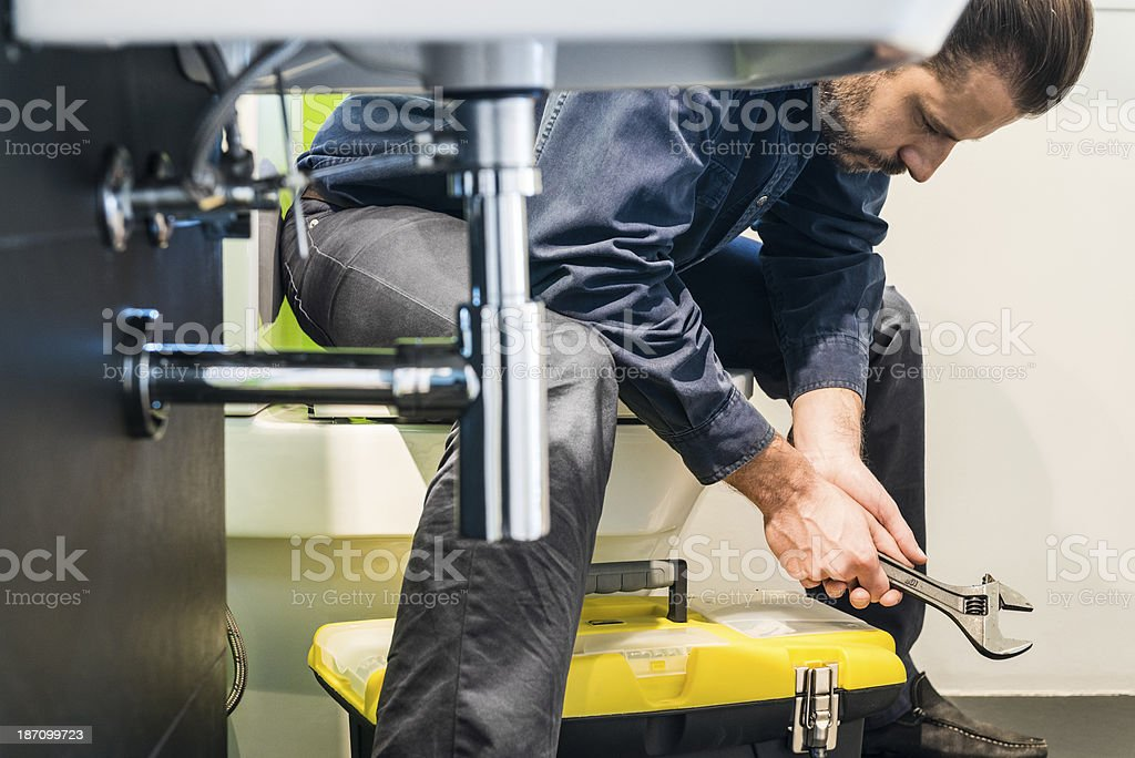 Plumber at work, sitting and thinking royalty-free stock photo