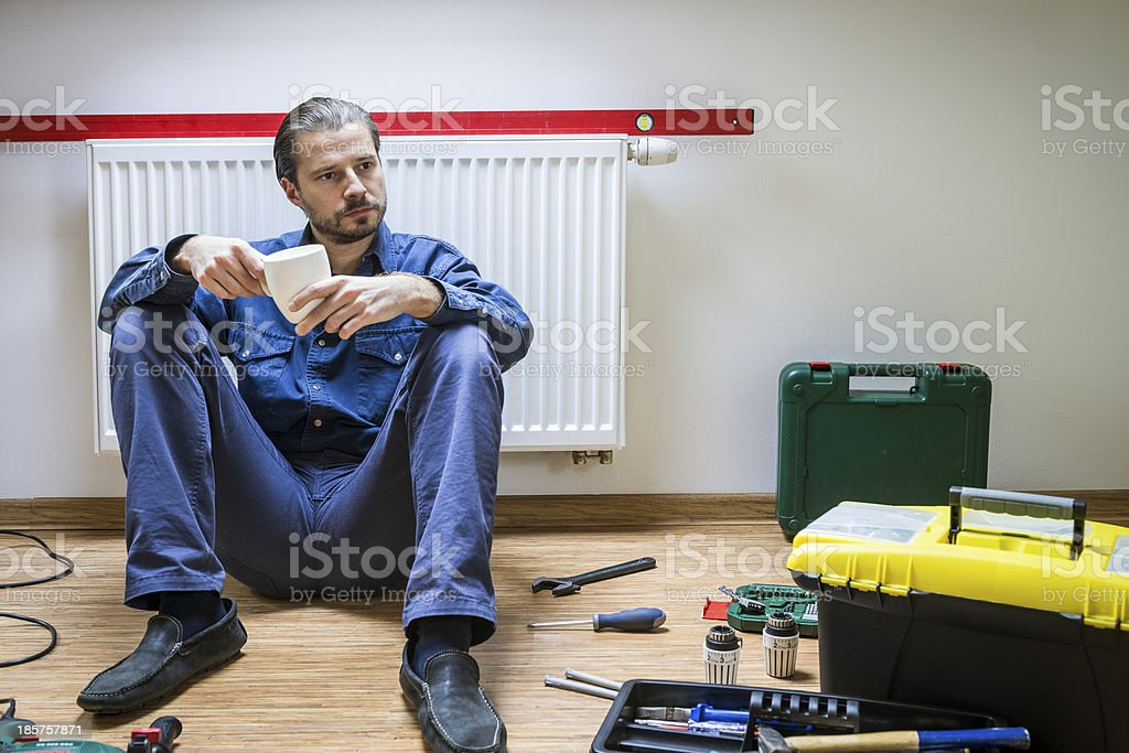 Plumber at work, tired, coffee break, sitting under the heater royalty-free stock photo