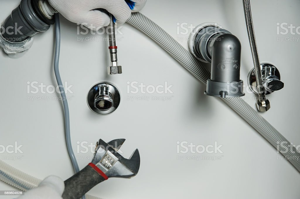 Plumber attaches flexible tube to the faucet. stock photo