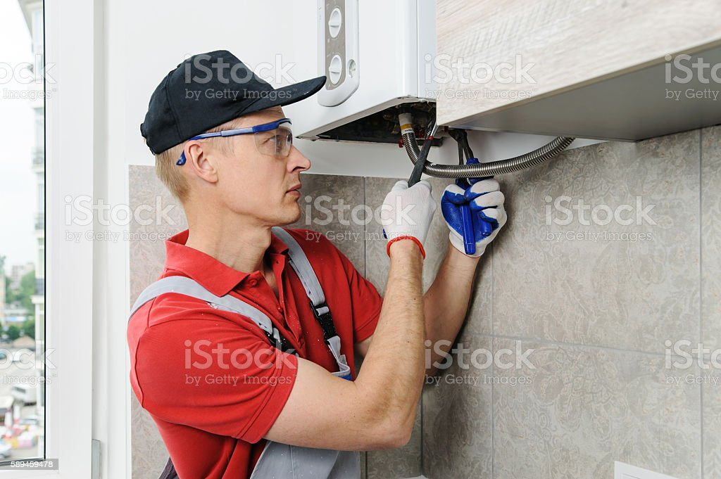 Plumber attaches to pipe gas boiler. stock photo