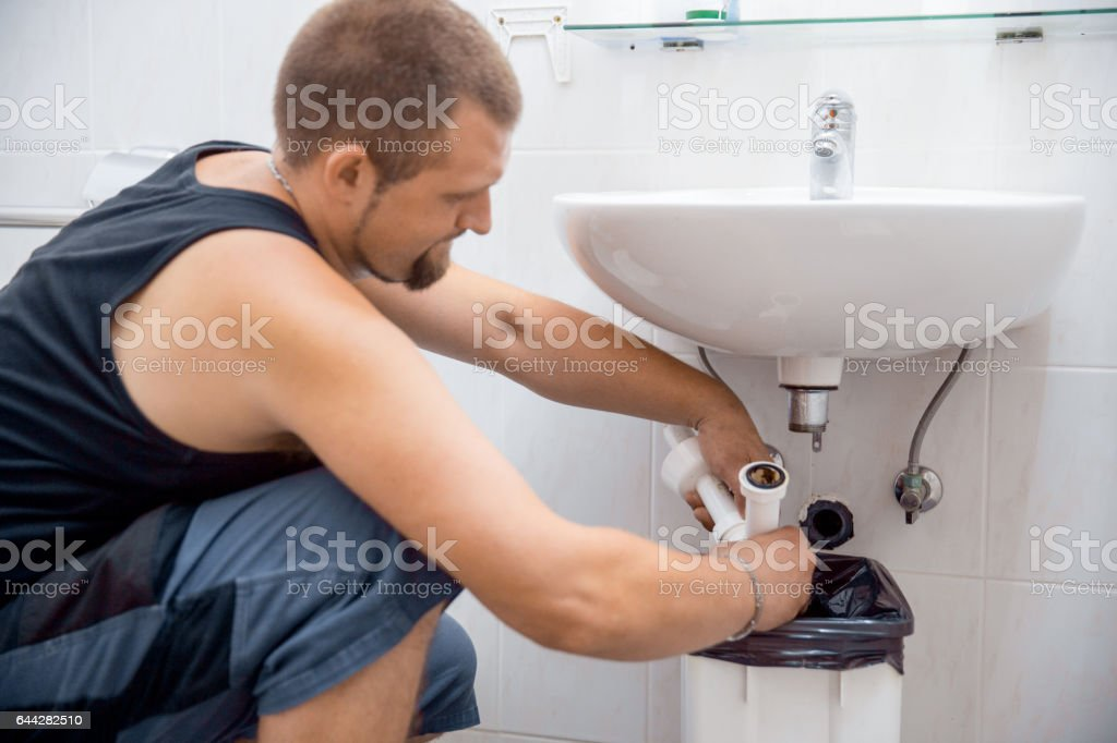 Plumber Cleaning The Pipe Tube stock photo