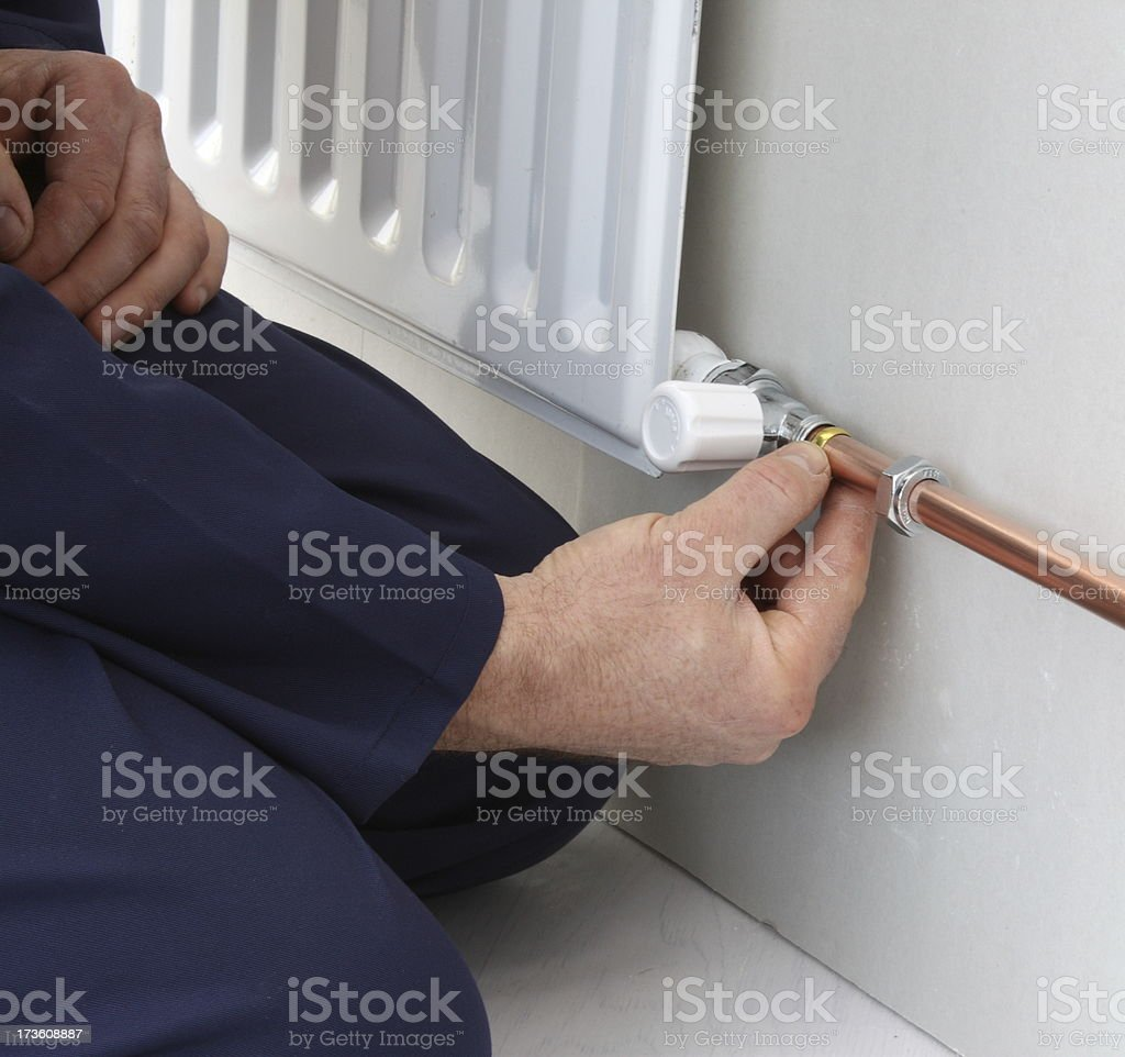 Plumber connecting up a central heating radiator royalty-free stock photo