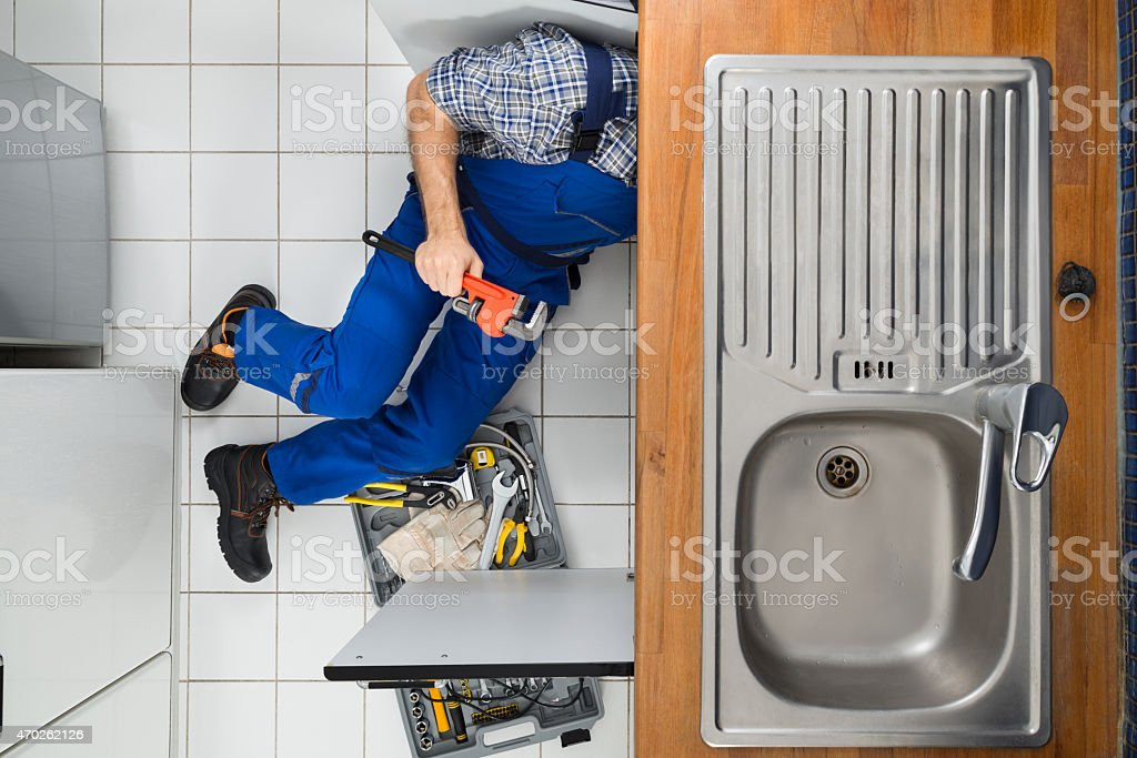 Plumber Examining Kitchen Sink stock photo