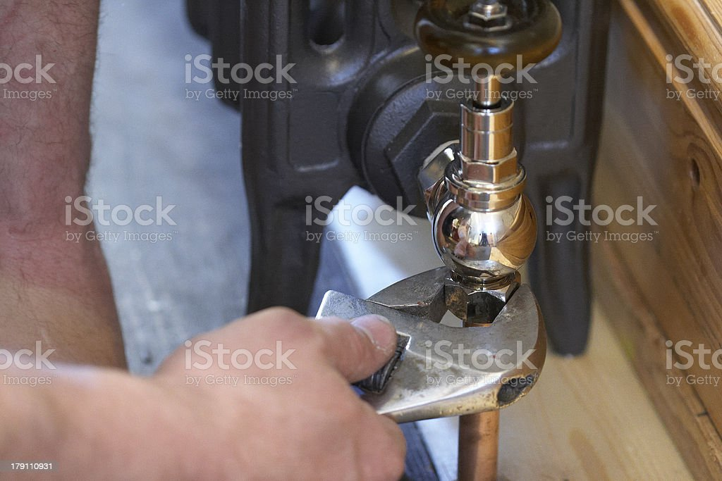 Plumber Fitting A New Radiator In House royalty-free stock photo