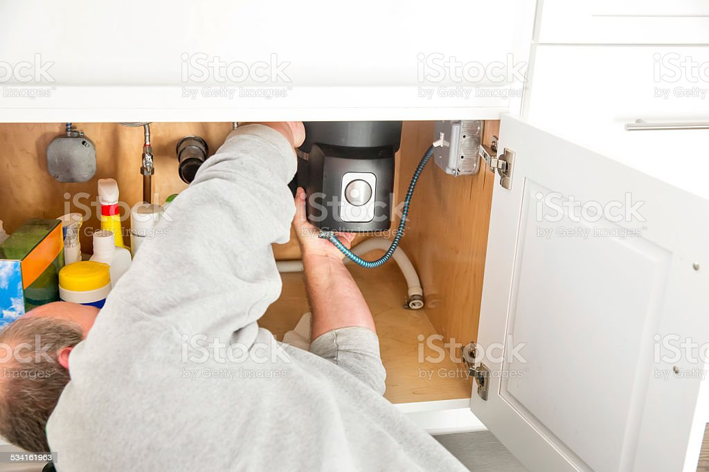 Plumber fixing a garbage disposal underneath a sink stock photo