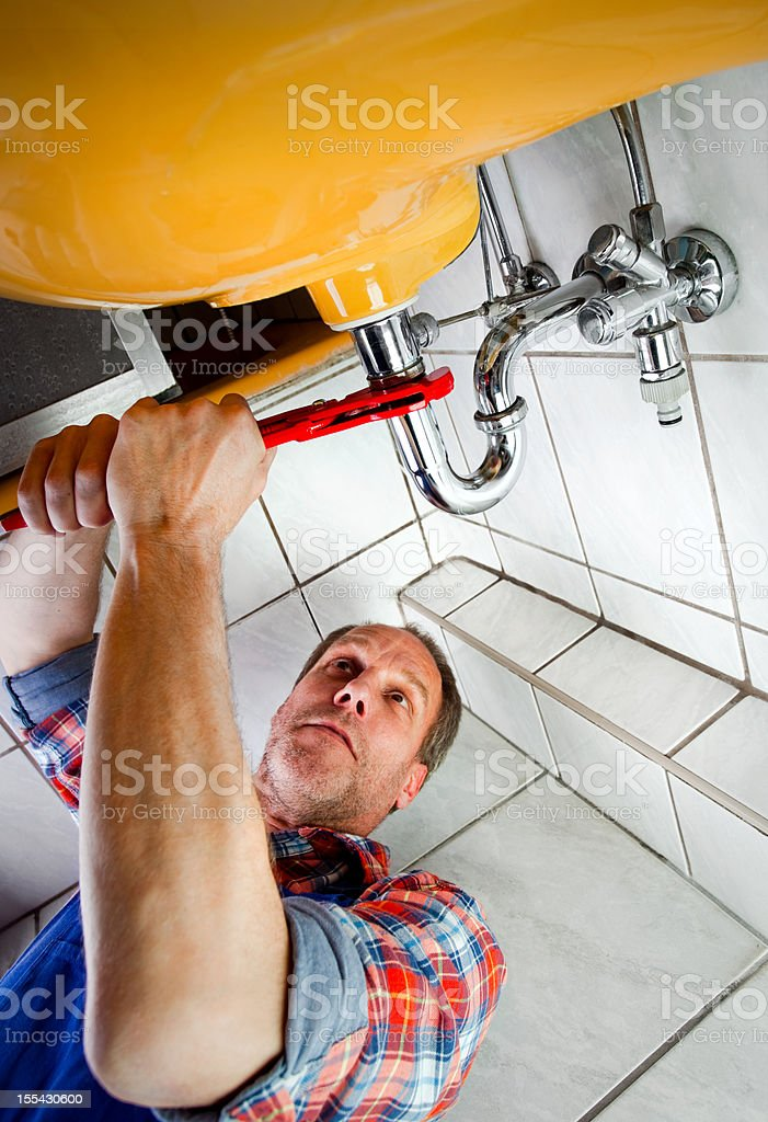 Plumber fixing a sink in bathroom royalty-free stock photo