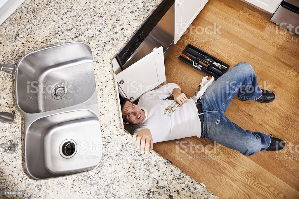 Plumber fixing kitchen sink stock photo