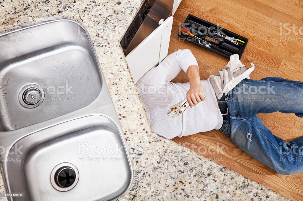 Plumber fixing kitchen sink royalty-free stock photo
