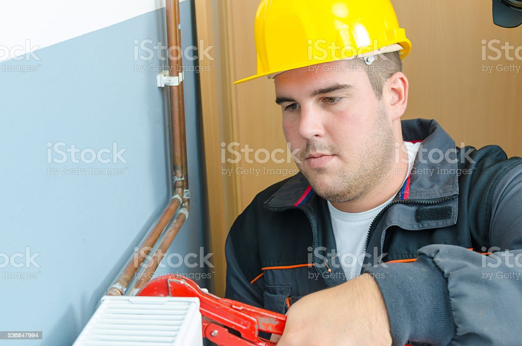 Plumber fixing radiator stock photo