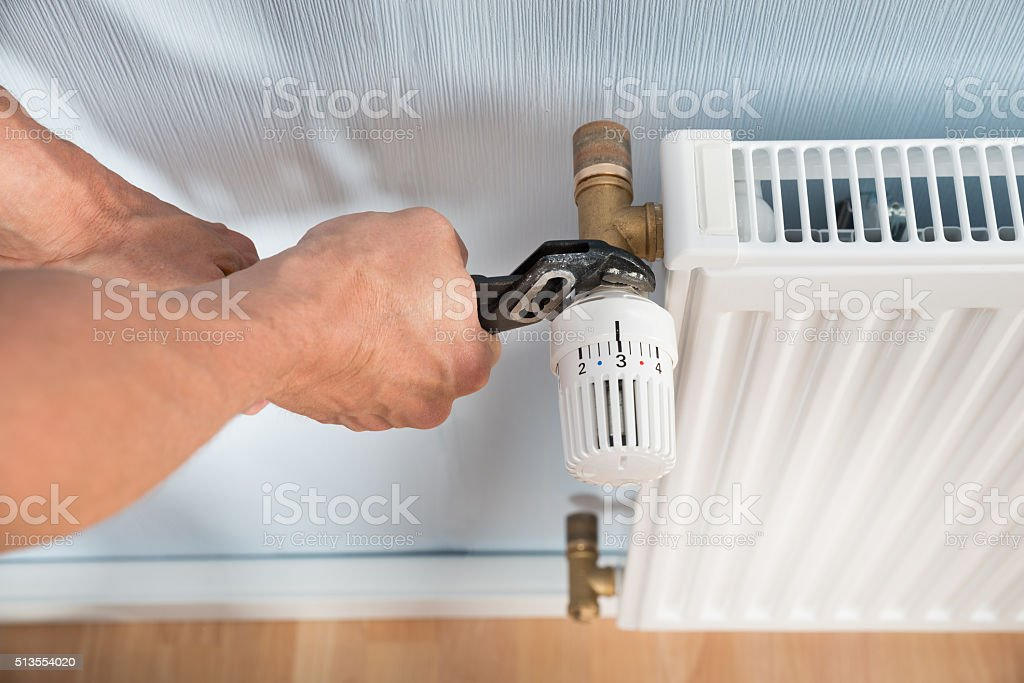 Plumber Fixing Radiator With Wrench stock photo