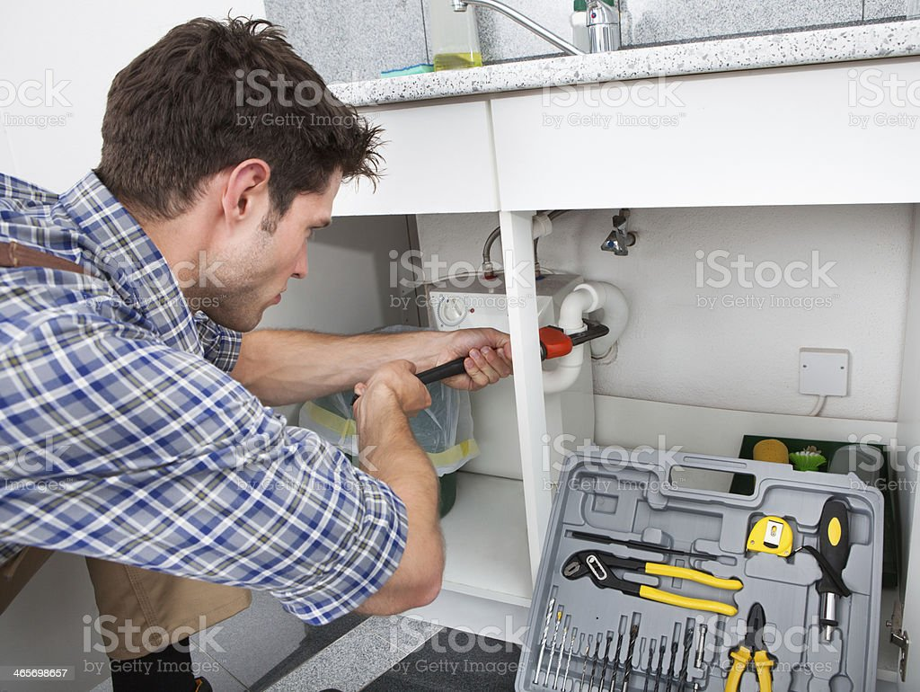 Plumber Fixing Sink In Kitchen stock photo