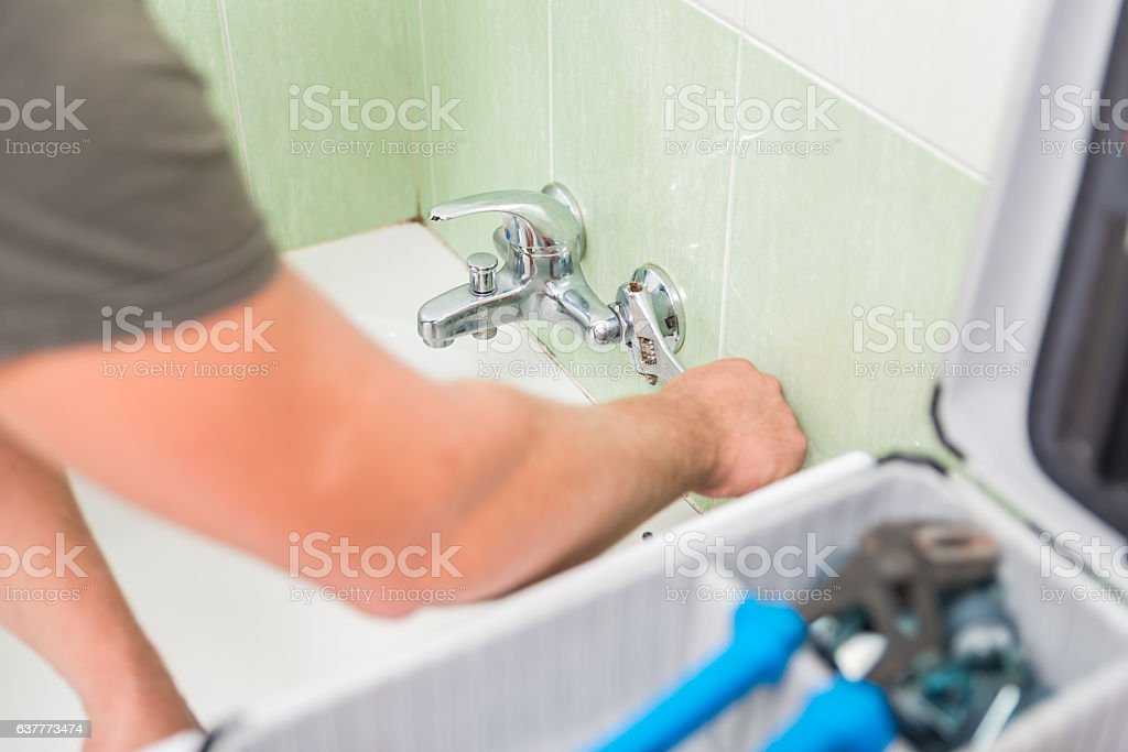 Plumber fixing the bathroom faucet stock photo