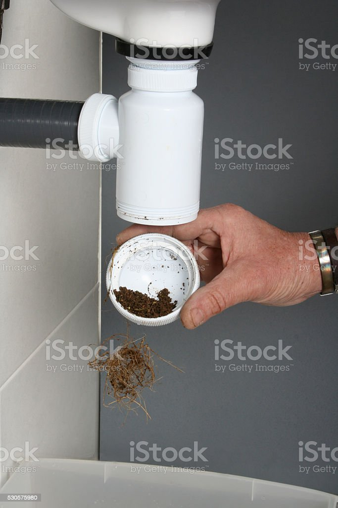 Plumber fixing the drain of a sink stock photo