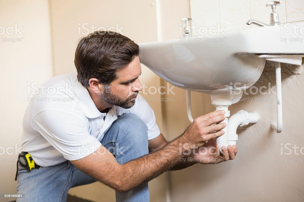 Plumber fixing the sink in a bathroom stock photo