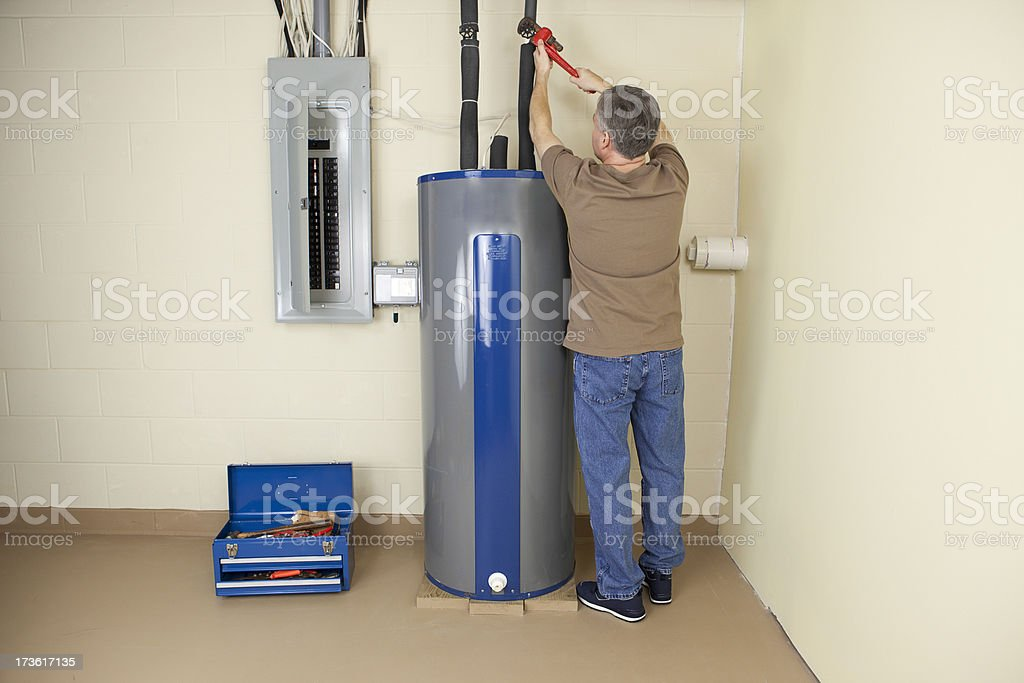 Plumber fixing Water Heater stock photo