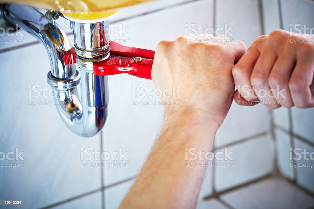 Plumber hands holding wrench and fixing a sink in bathroom royalty-free stock photo