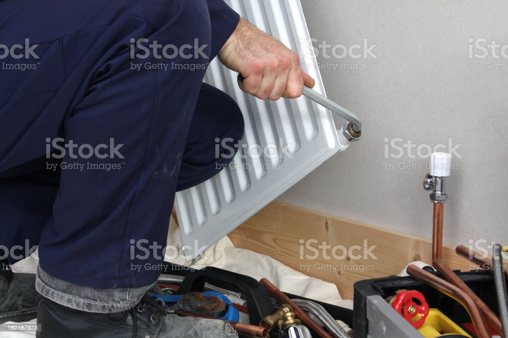Plumber installing a  radiator. royalty-free stock photo