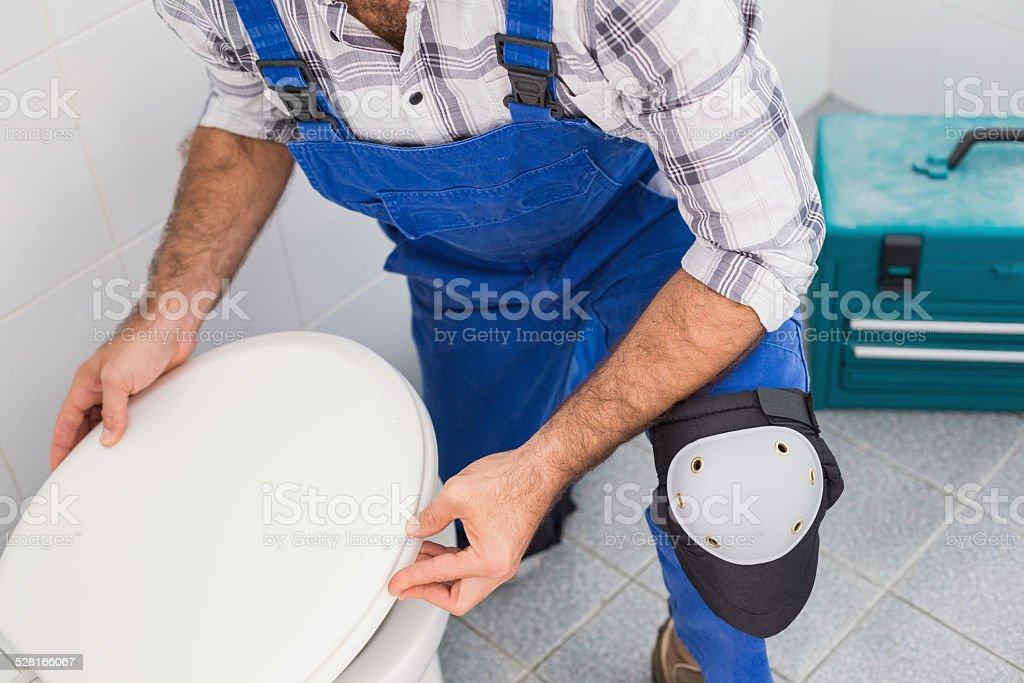 Plumber installing lid on toilet stock photo